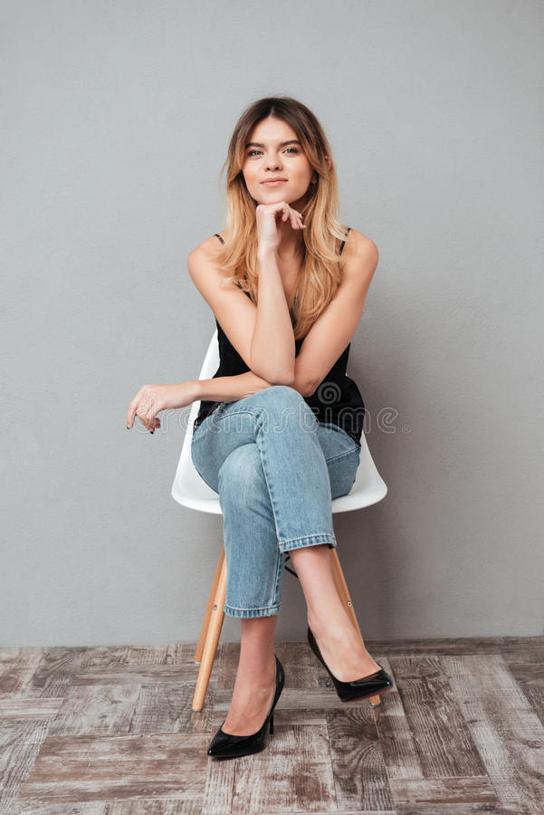 Retrato de una muchacha atractiva sonriente que se sienta en una silla fotos de archivo