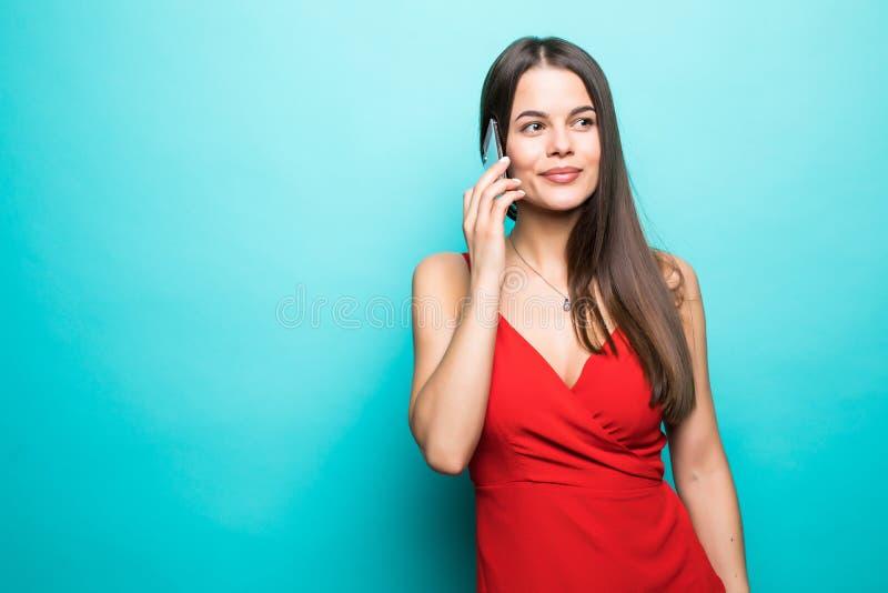 Retrato de una muchacha bastante alegre en vestido rojo que habla en el teléfono móvil aislado sobre fondo azul fotos de archivo