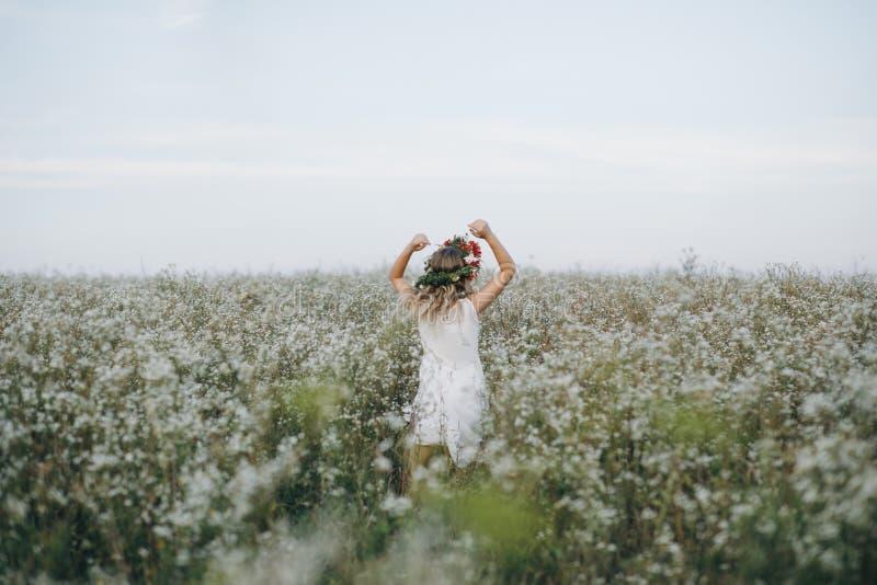 Retrato de una muchacha bastante rubia con los ojos azules con una guirnalda de flores en su cabeza que camina en campo con las f foto de archivo