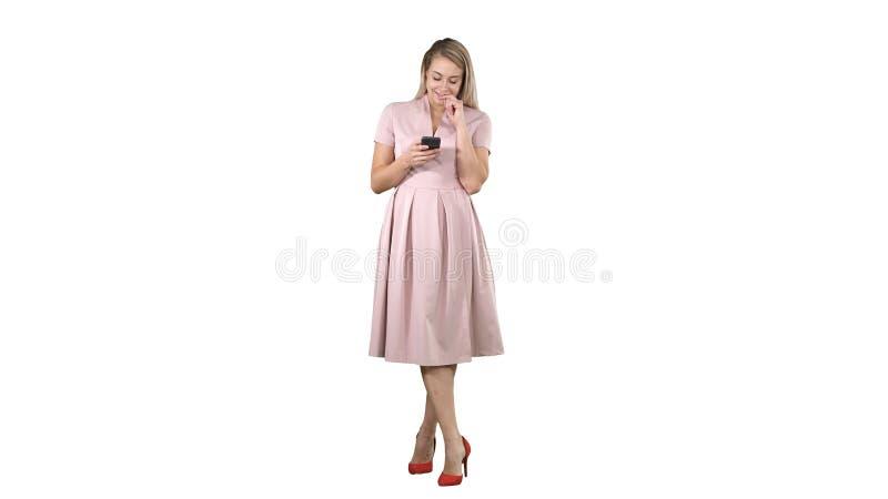 Retrato de una muchacha bastante sonriente en ropa del verano usando el teléfono móvil, mensaje que manda un SMS en el fondo blan imagen de archivo libre de regalías