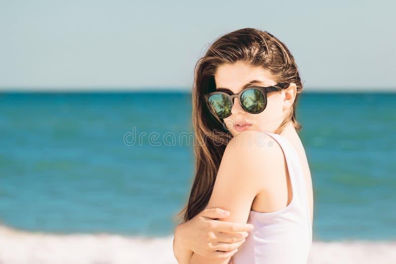 Retrato de una muchacha bonita con el pelo largo en gafas de sol de moda con la reflexi?n de las palmas que presenta en la playa foto de archivo libre de regalías