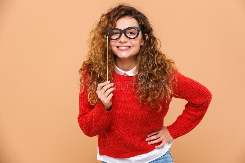 Retrato de una muchacha bonita feliz que sostiene las lentes falsas imagenes de archivo