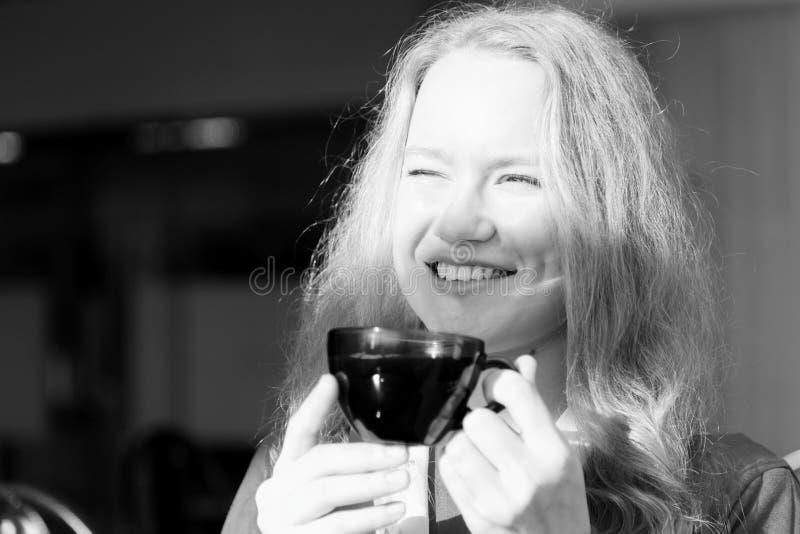 Retrato de una muchacha bonita joven con una taza de café que se sienta delante de la ventana en un día soleado Los rayos brillan imagenes de archivo