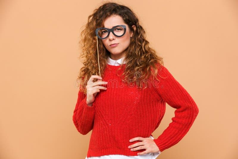 Retrato de una muchacha bonita joven que sostiene las lentes falsas foto de archivo libre de regalías