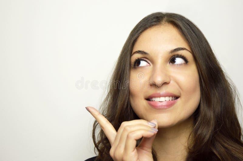Retrato de una muchacha bonita que señala el finger lejos aislado en un fondo blanco fotos de archivo libres de regalías