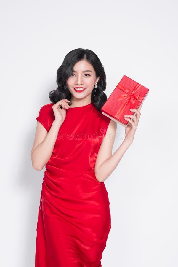 Retrato de una muchacha bonita sonriente que sostiene la caja de regalo roja imagen de archivo