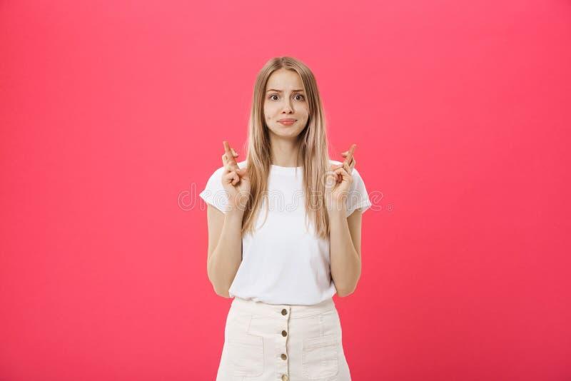 Retrato de una muchacha casual sonriente que sostiene los fingeres cruzados para la buena suerte aislado sobre fondo rosado imágenes de archivo libres de regalías