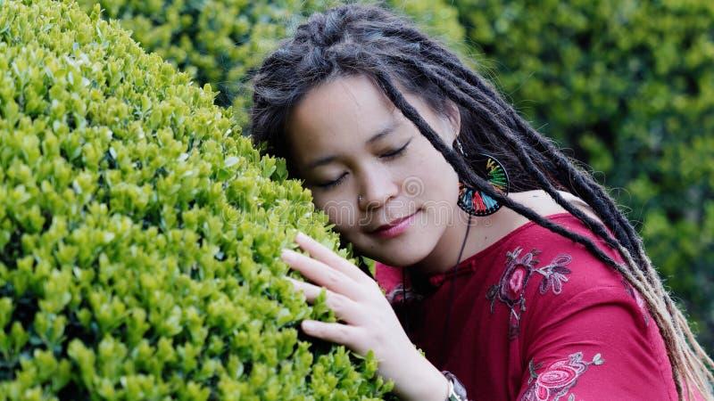 Retrato de una muchacha china hermosa con los dreadlocks lindos que abrazan arbustos verdes y que enumeran al sonido de la natura imagen de archivo libre de regalías