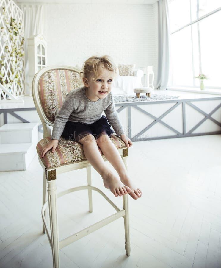 Retrato de una muchacha de cinco años feliz que se sienta en una silla en la sala de estar espaciosa foto de archivo libre de regalías