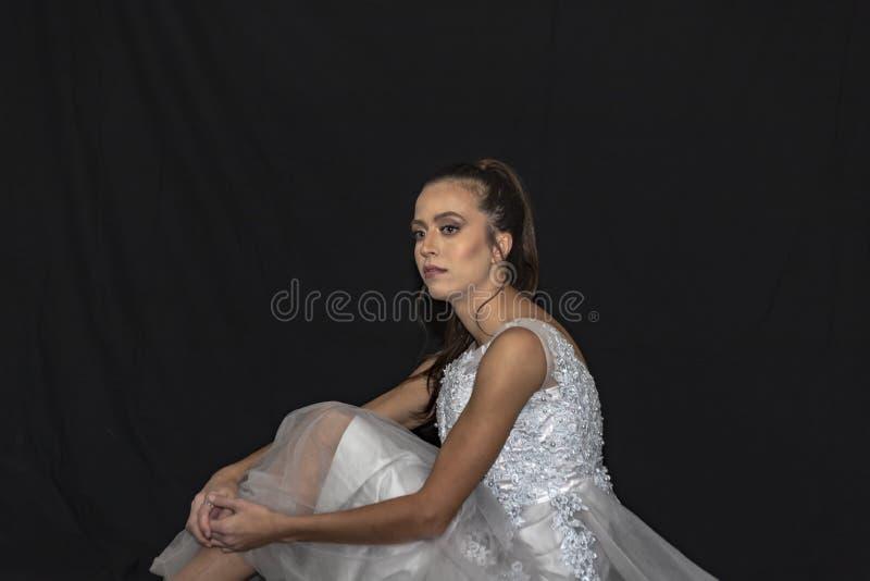 Retrato de una muchacha con el pelo largo y los ojos verdes en un vestido que se casa que se sienta en el piso Fondo negro imagenes de archivo