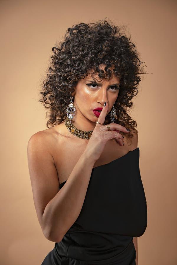 Retrato de una muchacha con el pelo rizado negro con maquillaje en un vestido de noche con un cierre para arriba imagen de archivo