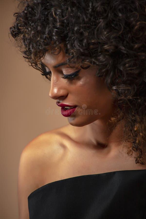 Retrato de una muchacha con el pelo rizado negro con maquillaje en un vestido de noche con un cierre para arriba imagenes de archivo