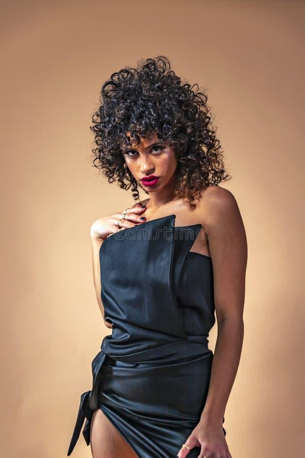 Retrato de una muchacha con el pelo rizado negro con maquillaje en un vestido de noche con un cierre para arriba fotos de archivo libres de regalías