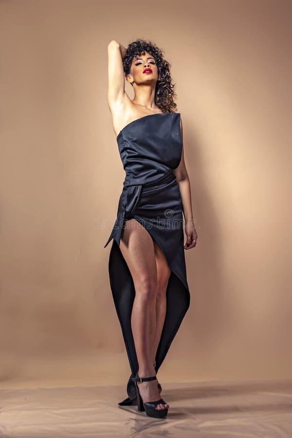 Retrato de una muchacha con el pelo rizado negro con maquillaje en un vestido de noche con un cierre para arriba foto de archivo