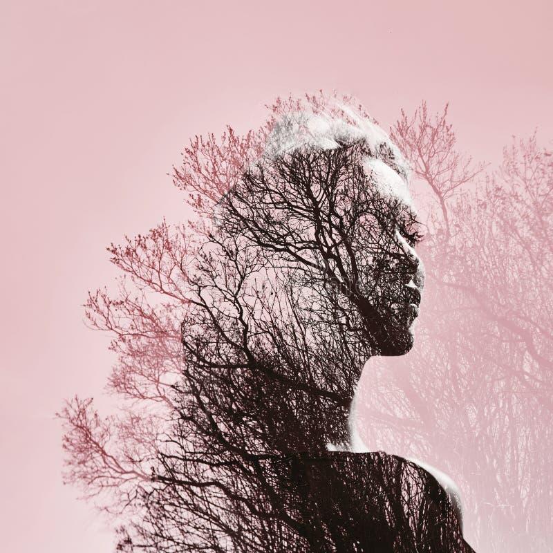 Retrato de una muchacha con la exposición doble contra una corona del árbol de foto de archivo libre de regalías