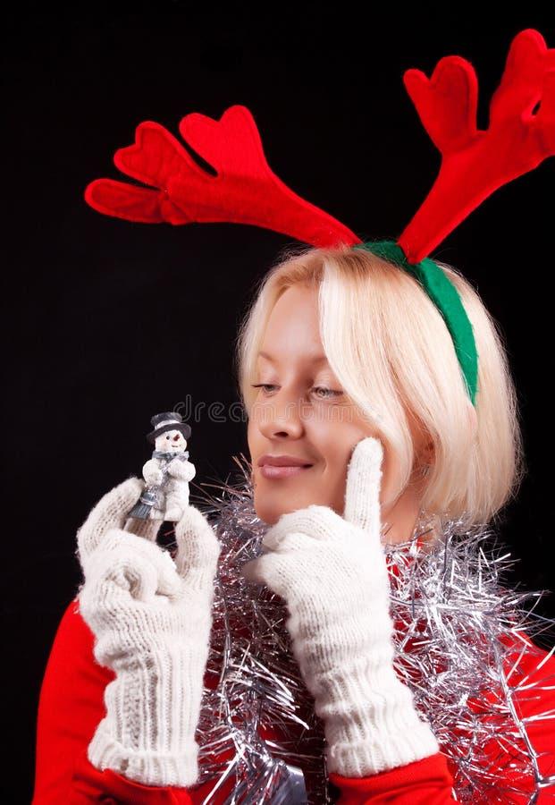 Retrato de una muchacha con los claxones y el muñeco de nieve fotografía de archivo