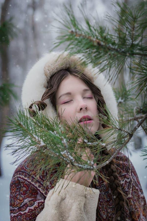 Retrato de una muchacha con los ojos cerrados en un abrigo de pieles cerca de un árbol de la conífera en un día de invierno fotografía de archivo libre de regalías