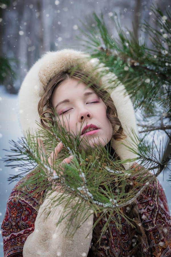 Retrato de una muchacha con los ojos cerrados en un abrigo de pieles cerca de un árbol de la conífera en un día de invierno imagenes de archivo