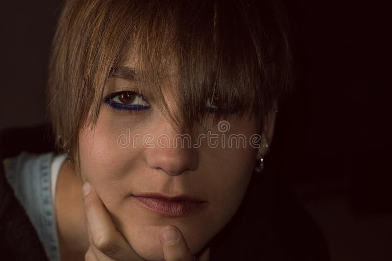 Retrato de una muchacha con su mano en su barbilla y una actitud pensativa imágenes de archivo libres de regalías