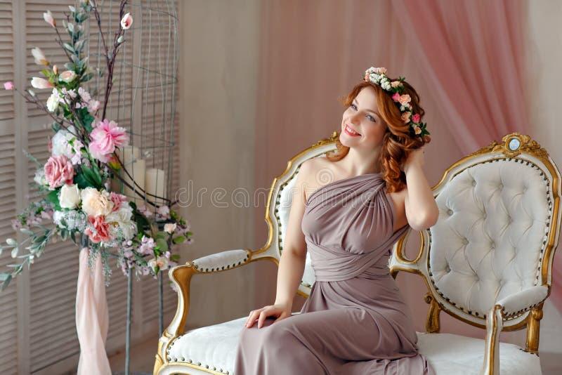 Retrato de una muchacha de risa pelirroja hermosa con una guirnalda o foto de archivo