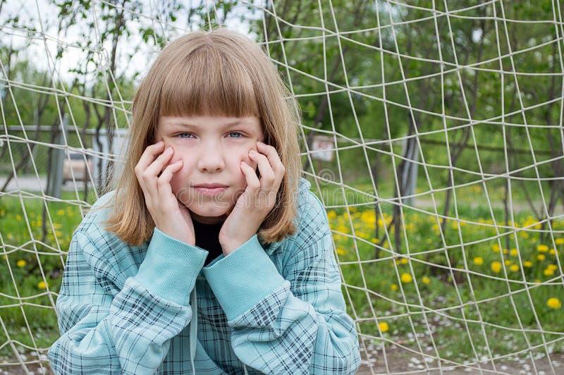Retrato de una muchacha delante de la rejilla foto de archivo