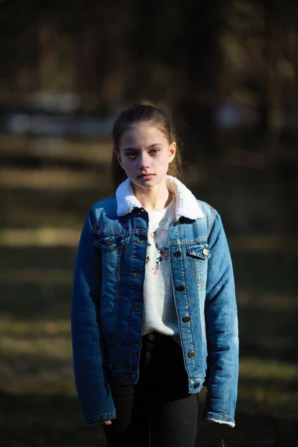 Retrato de una muchacha dulce doce-año-vieja en una chaqueta del dril de algodón foto de archivo libre de regalías