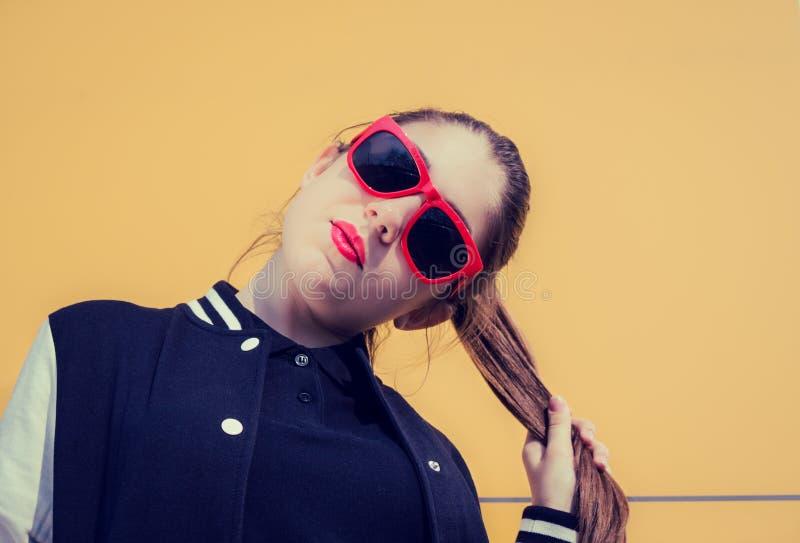Retrato de una muchacha elegante en gafas de sol rojas en un backgro amarillo imagenes de archivo