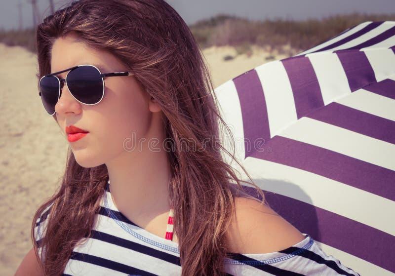 Retrato de una muchacha elegante en una camiseta rayada y las gafas de sol b imagen de archivo
