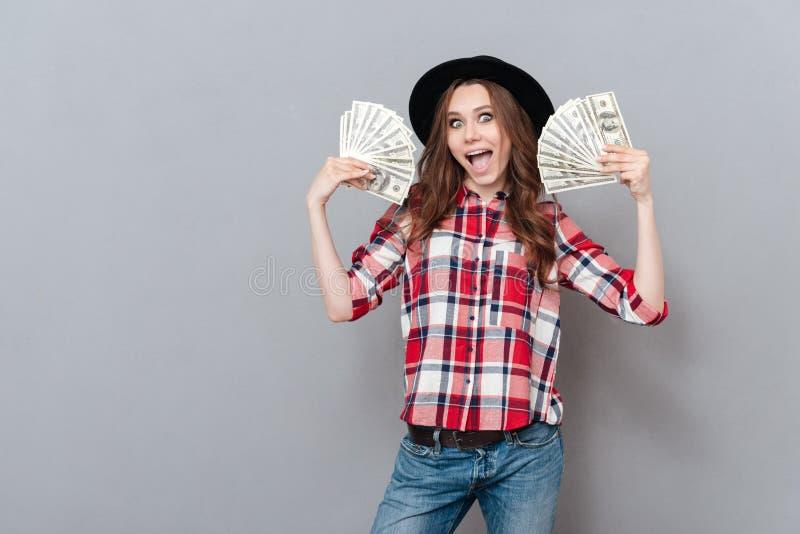 Retrato de una muchacha emocionada feliz que sostiene billetes de banco del dinero foto de archivo