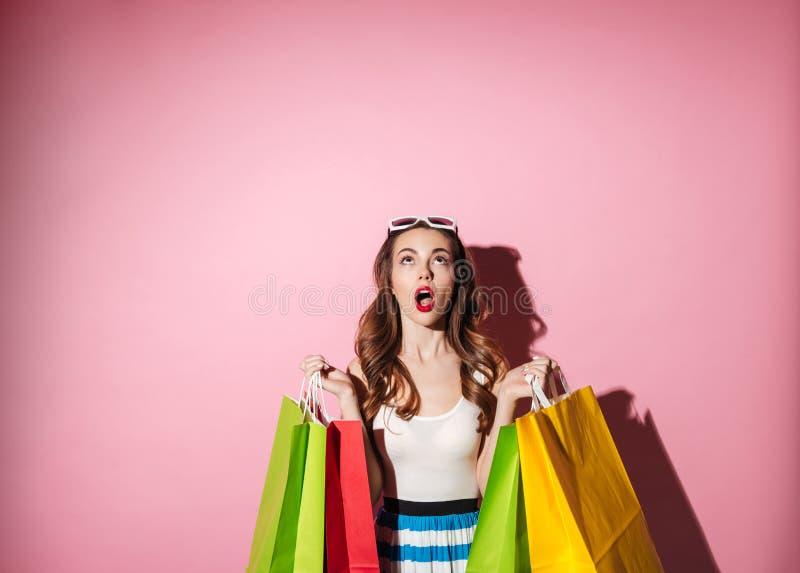Retrato de una muchacha emocionada linda que sostiene los panieres coloridos foto de archivo