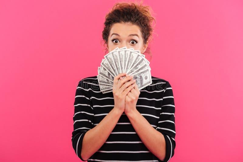 Retrato de una muchacha emocionada que sostiene el manojo de billetes de banco del dinero imagen de archivo