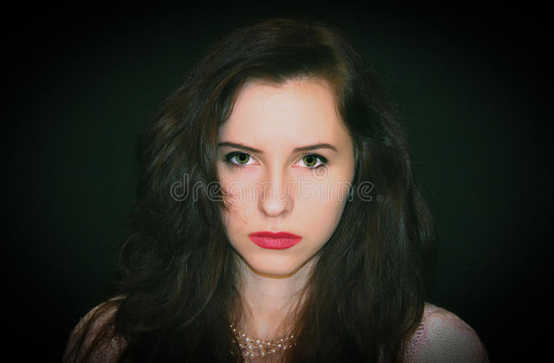 Retrato de una muchacha en un fondo negro, cólera de la emoción foto de archivo libre de regalías