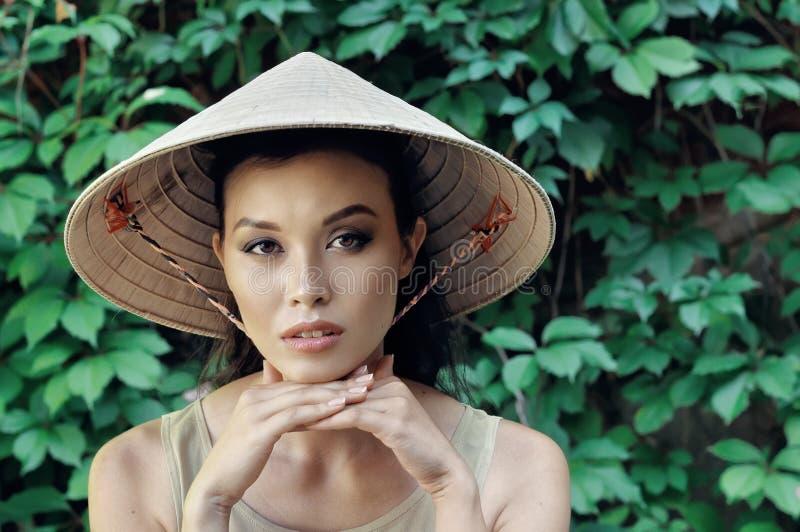 Retrato de una muchacha en un sombrero de paja imagenes de archivo