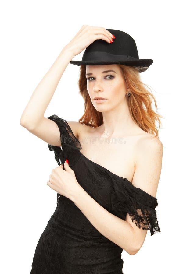 Retrato de una muchacha en un sombrero en un fondo blanco imagen de archivo