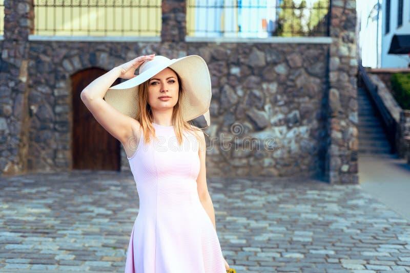 Retrato de una muchacha en un sombrero un vestido rosado foto de archivo