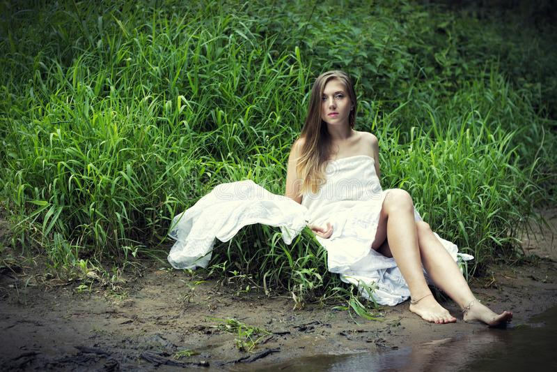 Retrato de una muchacha en un vestido blanco que se sienta en el fango en la orilla del río fotografía de archivo libre de regalías