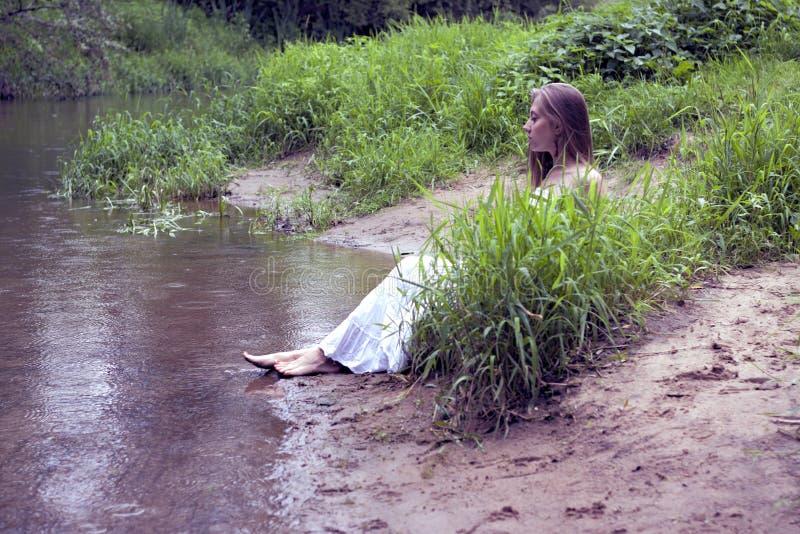 Retrato de una muchacha en un vestido blanco que se sienta en el fango en la orilla del río foto de archivo libre de regalías