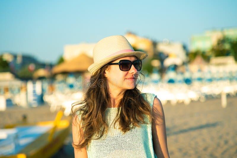 Retrato de una muchacha feliz en la playa por la mañana en la salida del sol fotos de archivo
