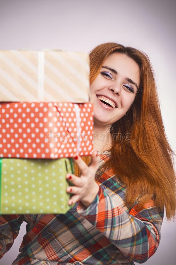 Retrato de una muchacha feliz hermosa con las porciones de regalos en manos, mujer joven que sostiene una pila de cajas envueltas imagenes de archivo