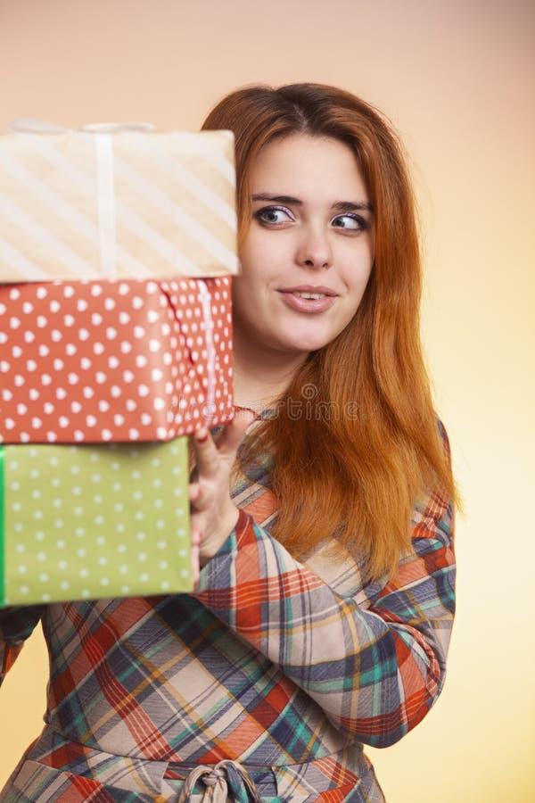 Retrato de una muchacha feliz hermosa con las porciones de regalos en manos, mujer joven que sostiene una pila de cajas envueltas foto de archivo