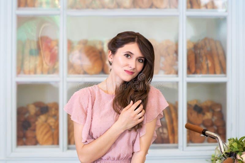 Retrato de una muchacha feliz hermosa joven con el pelo rizado largo en un vestido rosado contra la perspectiva de una ciudad eur foto de archivo