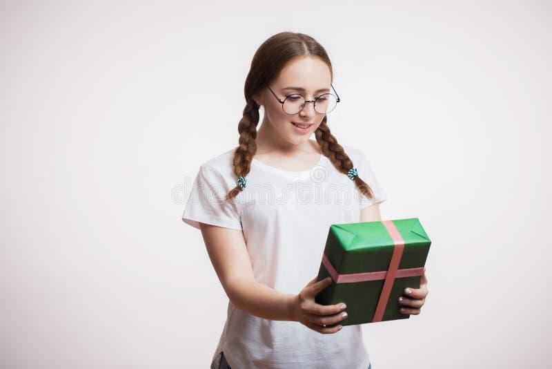 Retrato de una muchacha feliz joven que sostiene su regalo por Año Nuevo o cumpleaños Una mujer con vidrios y una camiseta es fel imágenes de archivo libres de regalías