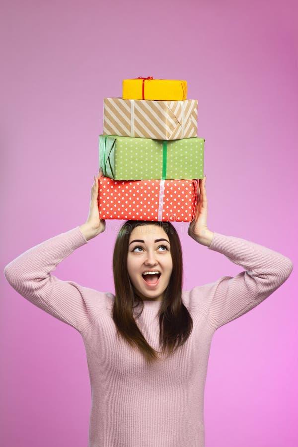 Retrato de una muchacha feliz de las cajas de regalo en su cabeza, mujer joven que lleva a cabo presentes en el documento decorat fotos de archivo