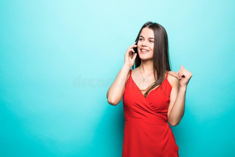Retrato de una muchacha feliz linda en vestido que habla en el teléfono móvil y de la risa aislada sobre fondo azul imagen de archivo