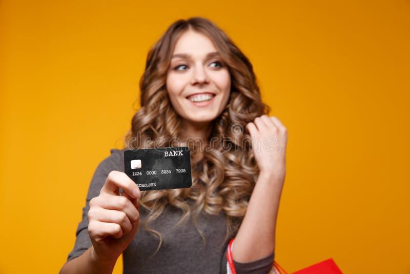 Retrato de una muchacha feliz sorprendida que sostiene bolsos de compras y que muestra la tarjeta de crédito mientras que mira la foto de archivo