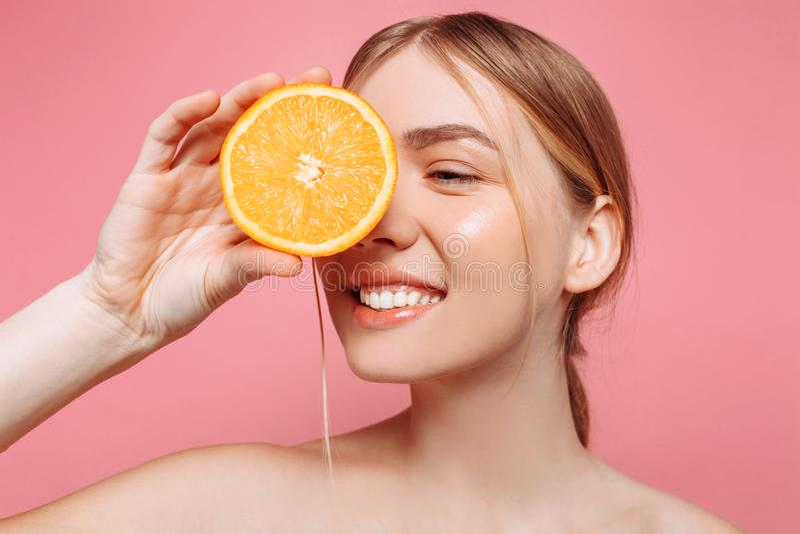 Retrato de una muchacha femenina, muchacha pura natural con una media naranja, cubriendo un ojo con una naranja imágenes de archivo libres de regalías