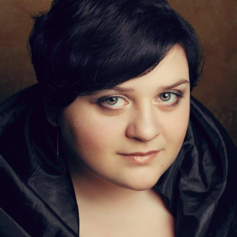 Retrato de una muchacha grande hermosa en un vestido negro con un seduc imagen de archivo