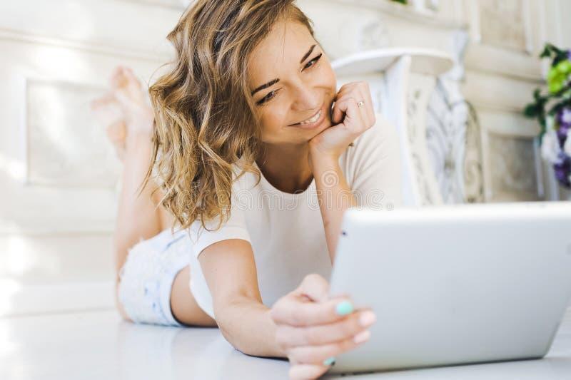 Retrato de una muchacha hermosa apacible, joven lindo, mentira atractiva en el piso, con la presentación del ordenador portátil imágenes de archivo libres de regalías