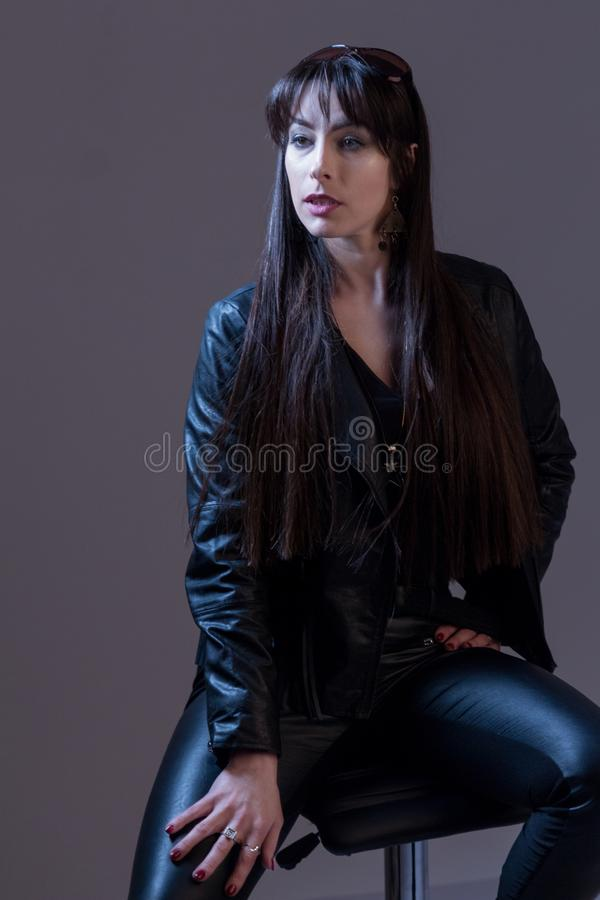 Retrato de una muchacha hermosa atractiva con el pelo largo en ropa de cuero negra Fotografía de la moda del estudio Fondo gris imagen de archivo libre de regalías