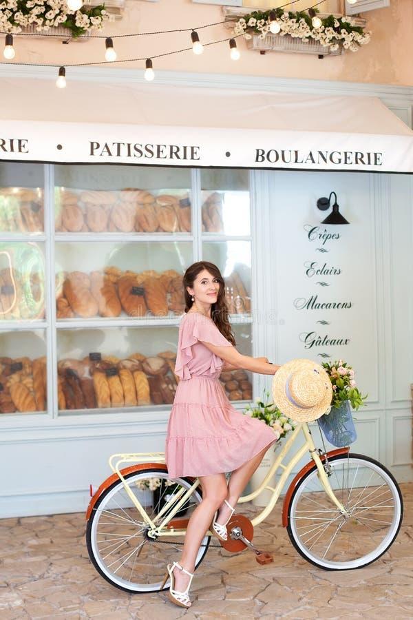 Retrato de una muchacha hermosa con el pelo rizado largo en un vestido que se sienta en una bicicleta retra amarilla en el fondo  fotografía de archivo
